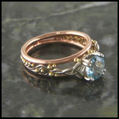 Custom 14K Rose Gold Celtic frame ring with 14K White Gold details and 18K Yellow Gold details is set with a 1.18 carat aquamarine. Original designs in 14K gold, elegantly suited as an engagement ring