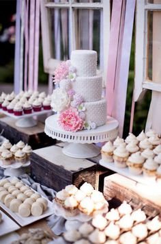 A chic dessert table is covered in miniature cupcakes with an elegant wedding cake serving as the focal point.