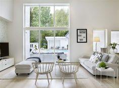 Fönstren från golv till tak släpper in mucket ljus och suddar ut gränsen mellan ute och inne. Matta, Ikea, bord, Scherlin, stolar, Yngve Ekström.