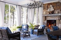 The fireplace anchoring the enclosed porch was crafted of local stone. The custom-made twig chandelier is by Paul Ferrante, the wicker seating and teak cocktail and dining tables are by Janus et Cie, and the white curtain and throwpillow fabric and the paisley used for the cushions are by Kravet. The custom-made outdoor rug is by Perennials.