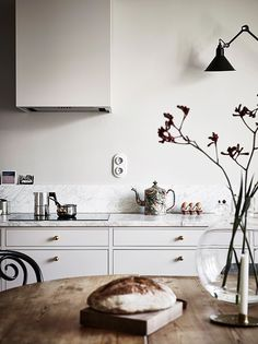 white kitchen with marble counter tops and black wall mounted light / sfgirlbybay
