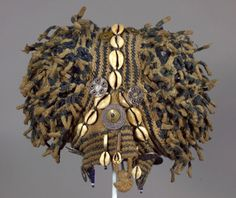 Africa | Man's Prestige Hat (ashetu) from the Bamum People of Cameroon  | 20th Century | Cotton, natural dyes, coins, cowrie shells | Finely knitted hats are the prerogative of titled individuals of the Grassland Kingdoms of southwestern Cameroon. This elaborate example has woven burls on either side that mimic a hairstyle once popular throughout the region.