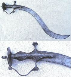 """""""Southern Indian Flamboyant"""", a variety of styles and ornamentation that were extremely ostentatious, blades with forked tips, greatly exaggerated curves or shoulders, and other unusual features. Many of these were likely for ornamentation. Tulwar hilted flamboyant sword, probably 19th c, with a koftgari work on the hilt, brass inlay on the blade. The most striking feature is a deeply recurved blade. The blade is sharpened along one-third of the back edge. Overall length, tip to tip 25…"""