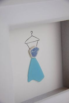 A unique sea glass art of a blue dress. The skirt is fashioned from rarer blue sea glass whilst the top is a lovely fragment of patterned blue and white beach pottery. Additional art in the picture is hand drawn in black ink. The picture is in a white wooden painted frame with a glass