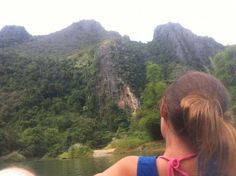 Classic over-the-shoulder shot of the amazing karst cliffs while tubing in Vang Vieng, Laos.