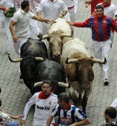 The Running of the Bulls, Pamplona, Spain.  Only a COMPLETE idiot would do this!