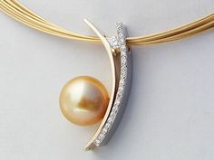 Rare, Golden Pearl set in a Hand-forged 14 karat Yellow & White Gold Pendant set with Pave Diamonds and a Tension Set Round Brilliant