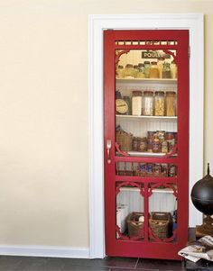 Painted red, this unique pantry door stands out against the white surfaces that surround it.