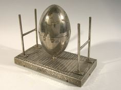 """Exquisite football figural music box c.1920-30s. Finely detailed silver plated music box features an oversized football shaped figural positioned at the center of a playing field gridiron with goal posts at either end. The playing field itself has highly ornate chased engravings throughout and the ball displays two player graphics at the center. The lid of the football opens to reveal interior musical works which plays """"Chicago."""" $1800"""