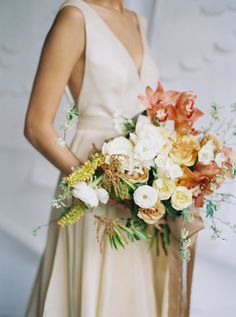 Beach inspiration for an indoor wedding fit for a modern, elegant bride. With warm blush tones and a off peach wedding dress, this bridal photoshoot will definitely inspire your elegant fall wedding. #fallweddinginspired #elegantbridalinspiration #beachweddings #weddingbouquets #modernbridalinspiration