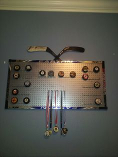 Made this out of broken sticks, peg board painted with spray paint and board hooks. Great for displaying medals and pucks!
