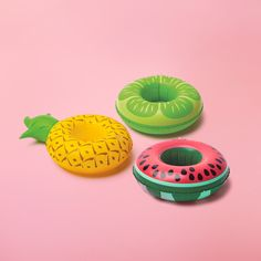 inflatable fruits drink floaties on pink background