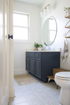 Our budget bathroom makeover is complete! Come see this transformed space with painted tile floors, a painted vanity, new mirror and more. I love the navy vanity, cement looking floor tiles, and brass vanity light #budgetbathroom #bathroommakeover Budget Bathroom, Bathroom Inspo, Master Bathroom, Bathroom Vanities, Bathroom Ideas, Design Your Own Bathroom, Bathroom Design Layout, Built In Shelves Living Room, Painted Vanity