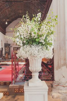 #Ceremony with large stone urn arrangements of delphinium, foliage and…