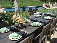 A long wood dining table is positioned on a patio near a large swimming pool, and has been set with plates, cutlery, and a gorgeous spring flowering bouquet centerpiece.