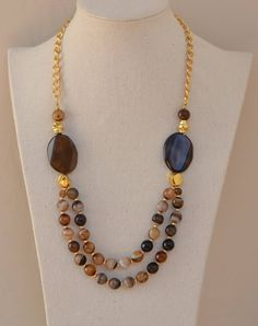 Necklace made with beads of agate Brown with Golden rockery entrepiezas. Top union of both stones in zamak gold strips. Flat stones of agates of 25 mm. x 15 mm. approximately. Chain adjustment with zamak gold clasp. With the chain necklace 42 cm. length can be varied up to 50 cm.
