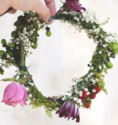 You could use fake flower stems to weave the crown, as they are wire covered by green. Then you could weave real flowers into the crown:)