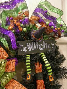 """Great Halloween colors of purple, orange, lime green and black are in this wreath. There are two large gathering bows with a striped foil deco mesh and a large triple looped bow. A sign stating """"The W"""