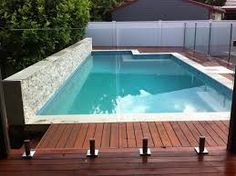 Image result for glass pool fence on sandstone retaining wall