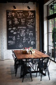 The chalkboard is the focal point in this industrial, rustic dining room. Those black chairs are AH-MAZING and don't get me started on the windows.. !