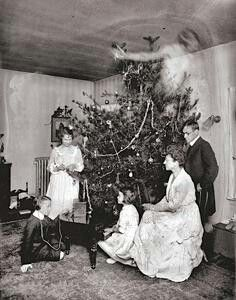 Ghost girl (?) floating above Christmas tree and family (vintage photograph)