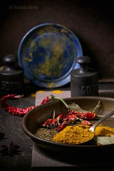 Tumeric and dry reh hot chili peppers on metal plate. Srved over dark table with vintage weight and blue ceramic plate.