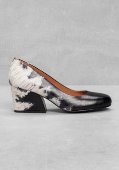 Crafted from leather, these mid-heel pumps feature a steady heel, a reptile-embossed finish, and an overall elegant look.