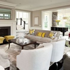 Gray, white, and yellow living room. The ottomans by the fireplace is an awesome idea... and I like the piece on the coffee table!