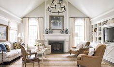 Living room with built in TV, and drapes with an arched transom window...