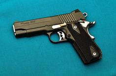 Sig Sauer 1911 Nightmare Carry  The compact variant of Sig's 1911 Nightmare. I'm not sure why it's called the Nightmare, I was thinking because it's finished in black Nitron finish. It could just be marketing to capitalize on cool or menacing names. Note the rounded bottom of the grip. Overall a nice .45 ACP pistol in the $800 range.
