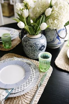 woven placemats, blue/navy plates, vases, tulips, hydrangeas