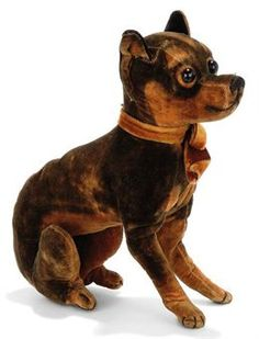 A SEATED VELVET CHIHUAHUA, brown and black, replaced boot button eyes and black stitching, circa 1910 --7in. (18cm.) high