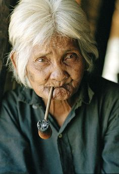 woman from the Jarai tribe of Cambodia smoking a pipe