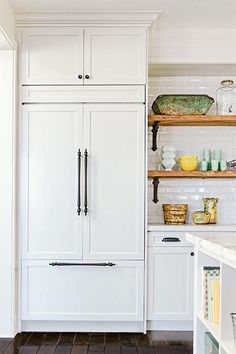 Custom panels help this built-in refrigerator melt into the surrounding all-white kitchen.