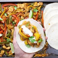 This is a photo of chicken fajitas being served with sour cream straight out of the sheet pan
