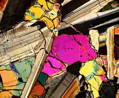 This is a photograph of an unclassified NWA Eucrite meteorite. This is a photo of a thin section of this meteorite viewed through a microscope using transmitted cross polarized light. The different colors indicate the mineral and crystal composition of this meteorite