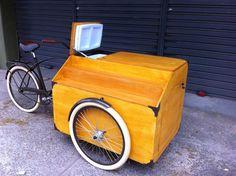 Triciclo para venda de comidas rápidas com expositor lateral tipo escada e caixa térmica embutida.