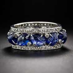 A rare and remarkable, original 1920s-30s vintage, eternity band rendered in platinum with classic Art Deco flair and sophistication. The center row is composed of eleven rich crystalline blue cabochon sapphires, most of which are hand-carved a la the noted tutti-frutti style, totaling 7.50 carats and dotted here and there with tiny collet-set single-cut diamonds.