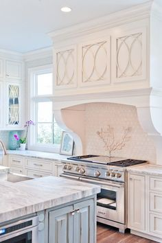 The palest hint of pink in this kitchen counteracts the cool white and gray tones that otherwise dominate the palette here.