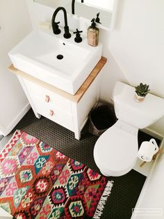 bathroom with white walls, black floors, and colorful rug.