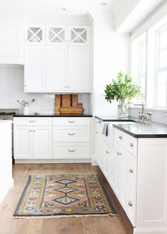 White cupboards, black counter tops, silver sink, clear vase, wooden floors, colorful rug, tiled white walls