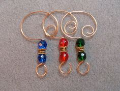 =^..^= This item is a set of 12 strong handcrafted Ornament Enhancers Hangers Hooks made using heavy gold plated wire. 4 each of 3 colors: Red, Blue, Green Each has been carefully handmade by me using: 8mm Faceted Firepolished glass beads. Gold plated spacer bead 18 gauge sturdy German