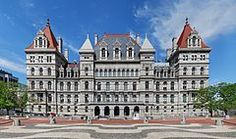 NYS Capitol - An ornate building, several stories high, of light colored stone. Many arches are visible on its front. On its sides are two large towers wi...