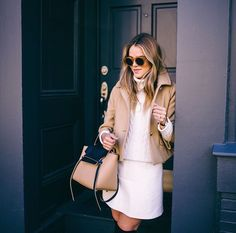 Julia Engel from Gal Meets Glam - perfect in neutral tones - camel colored coat, cream turtleneck sweater, and pale pink mini skirt
