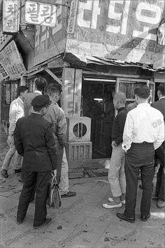 1964년 10월 토쿄올림픽 중계를 라디오로 듣고 있는 사람들
