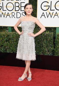 Wearing an embellished Jenny Packham dress with playful metallic Sophia Webster sandals.              Image...