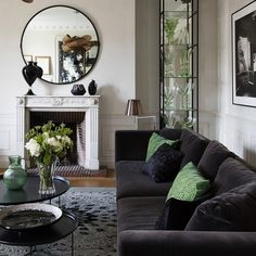 Un grand canapé noir accueille dans le salon de cendrine dominguez avec une cheminée en marbre et un miroir très design tout rond
