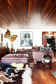 Boho inspired living room with wood ceilings and floors, a velvet sectional, and a large shag rug