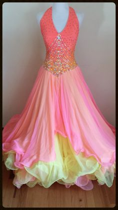 Dore Designs Smooth/Standard dress in tropical pink, yellow and orange.  Heavily decorated bodice with Swarovski stones and pearls.  Full skirt with multiple layers of chiffon and crinoline and flowing chiffon scarves down the back.  Full bodysuit and cups to a C. Fits sizes 2-4-6 Height suggestion:
