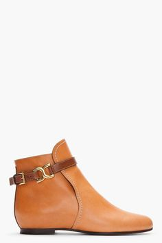 Chloe Tan Leather Marcie Flat Boots -  Chloe Tan Leather Marcie Flat Boots Chloe Buffed leather flat ankle boots in tan. Round toe. Gold tone hardware. Elasticized strap under extended tongue. White stitching at tongue. Contrast brown leather strap at ankle with logo clasp and pin buckle closure. White stitching. Price $895.00 Click...